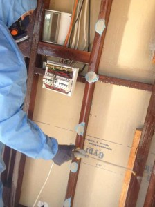 Photo of CCS worker spraying a mixture of PVC glue and water to seal in any particles